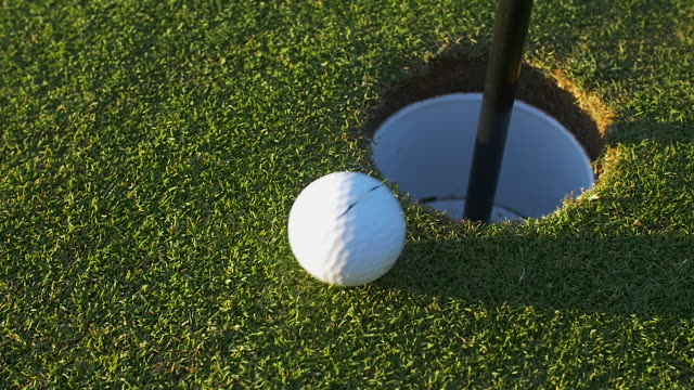 golf ball travels in to hole. - green golf course stock videos and b-roll footage