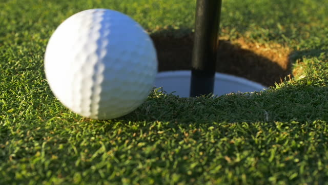 golf ball travels in to hole. - golf ball stock videos and b-roll footage