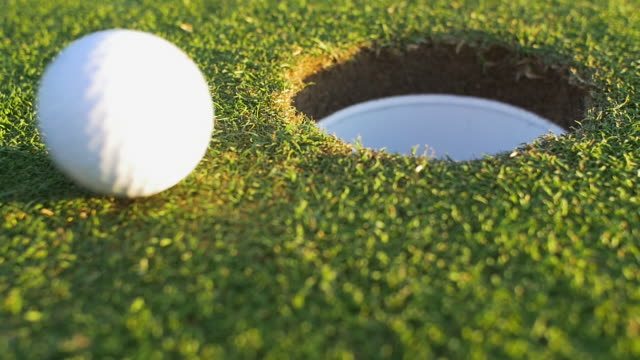 Golf ball travels in to hole.