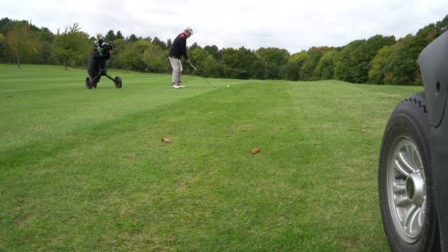 vídeos de stock, filmes e b-roll de a golf buggy drives up to the ball on the fairway. from a low angle. - bolsa de golfe