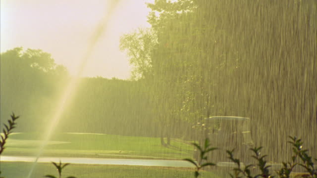 ms, pan, golf carts riding past sprinklers on golf course, seco, maine, usa - sprinkler stock-videos und b-roll-filmmaterial