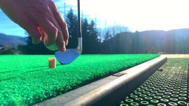 golf club epon af-705 and golf swing on the golf ball on mat on driving range with sunlight in switzerland. - drive ball sports stock videos & royalty-free footage
