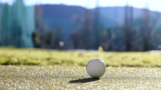 golf club epon af705 and golf swing on the golf ball with sunlight in switzerland - low section stock videos & royalty-free footage
