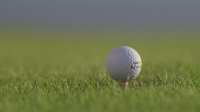 A golf club hits a golf ball.