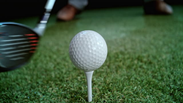 slo mo golf club hitting the ball - golf ball stock videos & royalty-free footage
