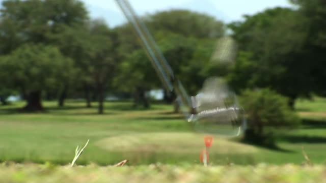 a golf club smacks a golf ball off a tee and sends ball and tee flying. - golf ball stock videos & royalty-free footage