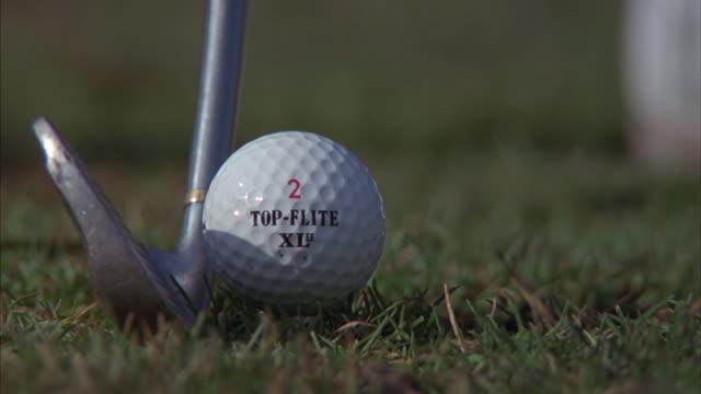 A golf club strikes a golf ball off a tee.