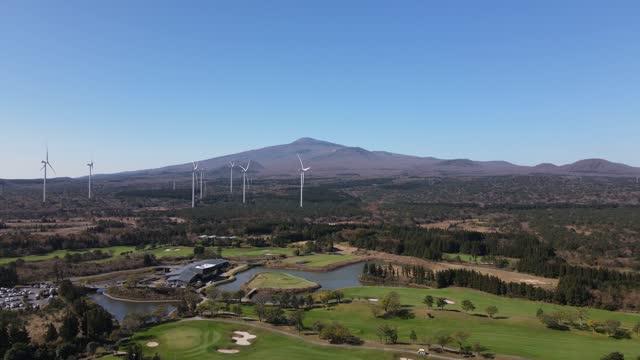 vídeos de stock, filmes e b-roll de golf course and wind turbine with hallasan mountain in background / seogwipo-si, jeju-do, south korea - obstáculo de água