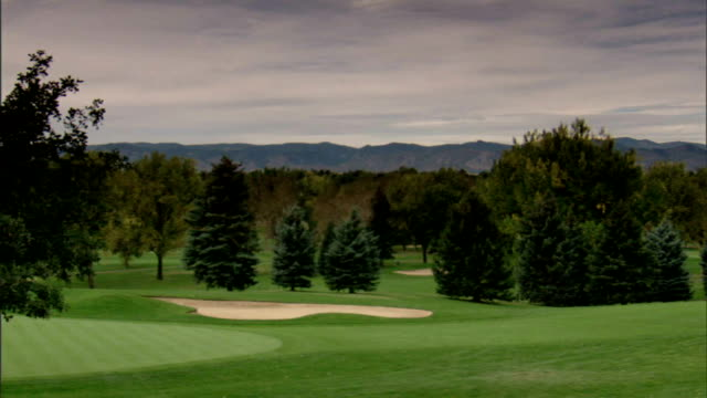 PAN Golf course landscaping trees w/ purple Rocky Mountains distant BG first tee golf cart road