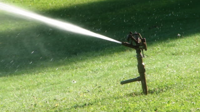 golf course lawn sprinkler in action - sprinkler system stock videos & royalty-free footage