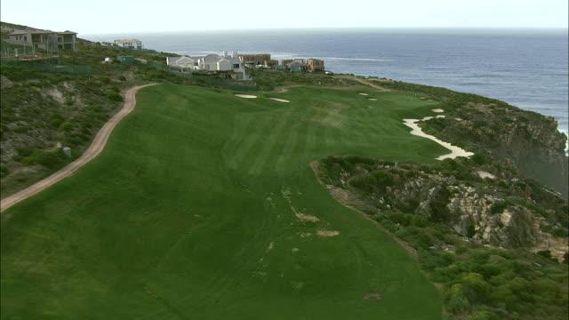 vídeos y material grabado en eventos de stock de golf course nestled on a jagged cliff next to the ocean - green de golf
