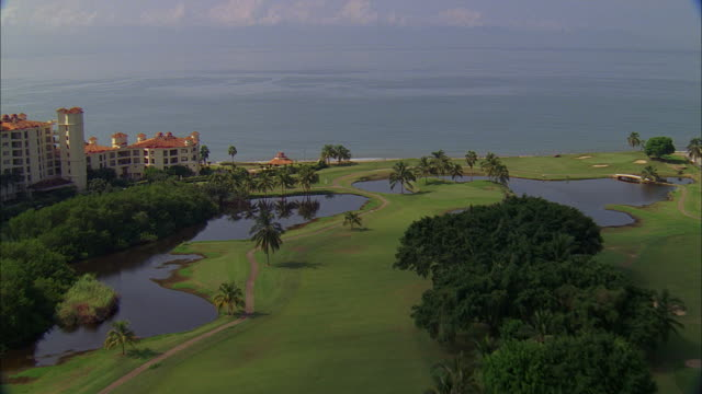 AERIAL Golf course, shoreline, sandy beach and gentle waves, and a coastal hotel with red tile roof and swimming pool