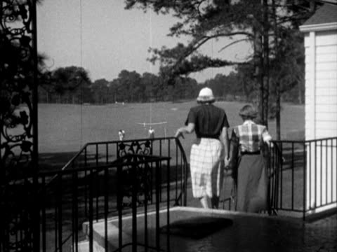 Golf course w/ female male golfing preparing to putt on green clubhouse BG BEHIND Female members walking down steps toward course waving to Ann Fred...
