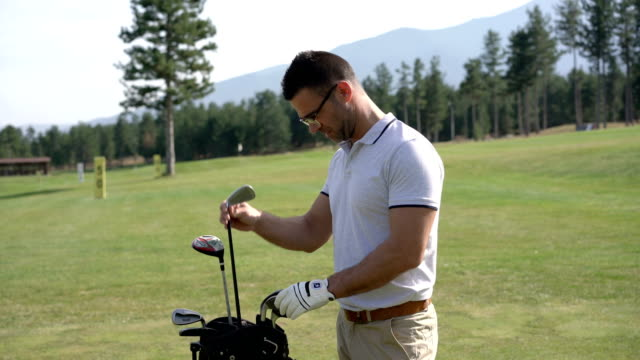 golf player at the golf course picking new club from his bag - scegliere video stock e b–roll
