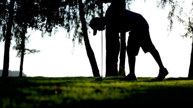 golfspeler maken tee off op een golfbaan, silhouet