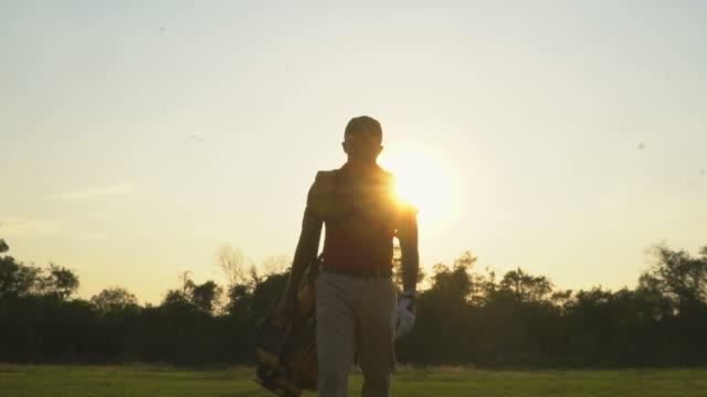 ゴルフバッグでフェアウェイに沿って歩くゴルフプレーヤー - ゴルフのスウィング点の映像素材/bロール