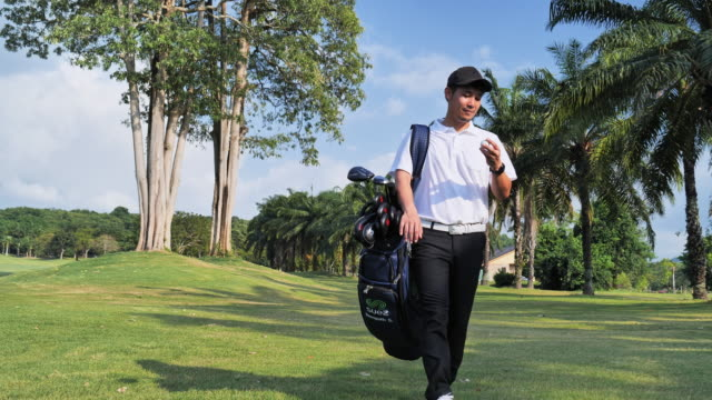 golf player walking and carrying bag on course during summer game golfing - bunker stock videos & royalty-free footage