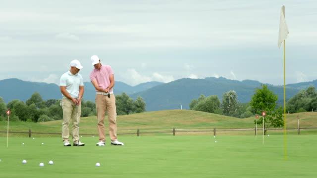 vídeos y material grabado en eventos de stock de dolly hd: pro enseñanza macho jugador de golf - deporte profesional
