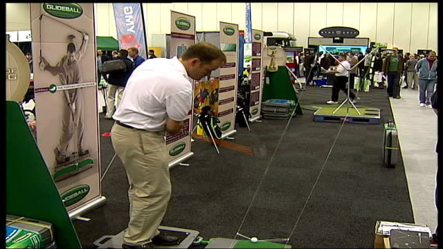 golf show at docklands: ronnie corbett interview; england: london: docklands: int dean davies practising golf shot gvs stalls selling golf clubs... - golf swing stock videos & royalty-free footage
