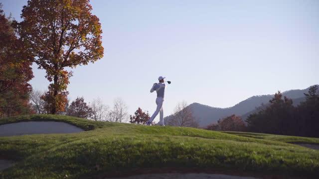 vídeos y material grabado en eventos de stock de golf - young man swinging with driver - alto descripción física