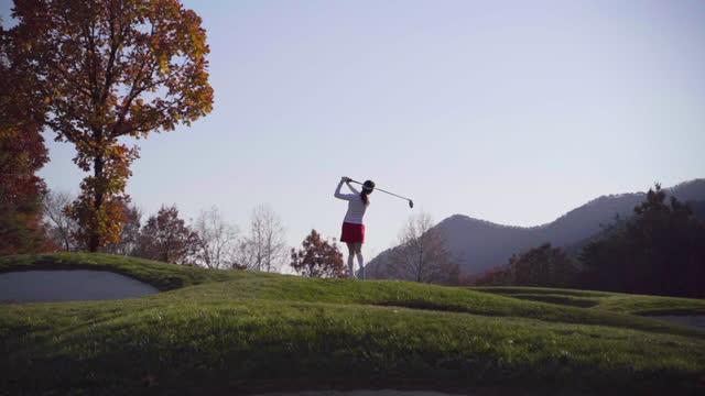 vidéos et rushes de golf - young woman swinging with driver - golf