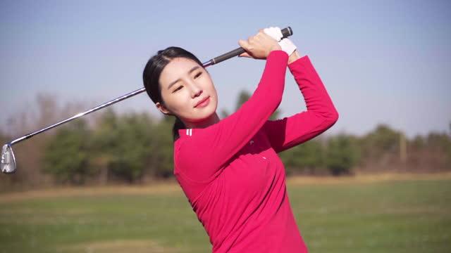 golf - young woman swinging with iron - ゴルフのスウィング点の映像素材/bロール