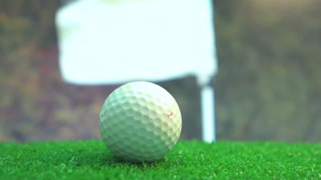 vidéos et rushes de golfball sur vert contre le beau ciel bleu - tee de golf