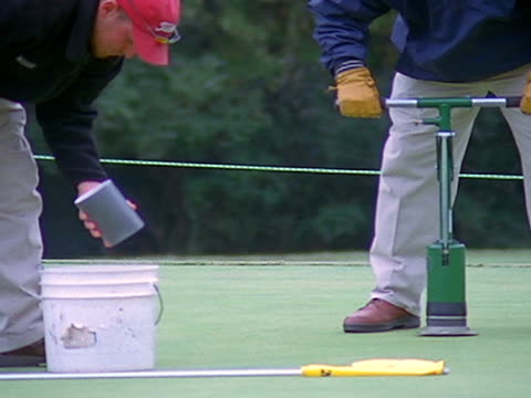 golf-course workers use hole-digger to create hole on the putting green. - putting green stock videos & royalty-free footage