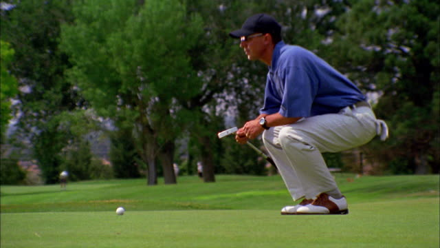 vídeos y material grabado en eventos de stock de a golfer aims then lines up on a green. - putt