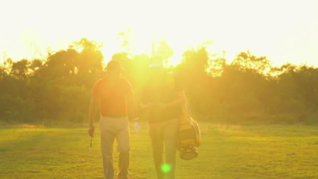 golfer and caddy - golf bag stock videos & royalty-free footage