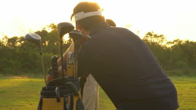 stockvideo's en b-roll-footage met golfer en caddy - golf sport