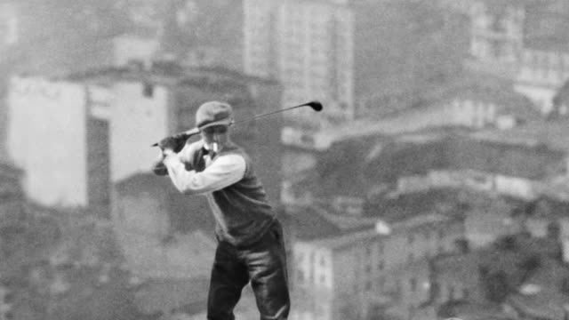 A golfer and his caddy tee off the girder of a skyscraper under construction.
