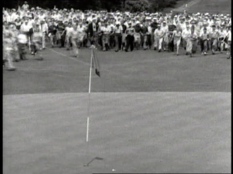 vidéos et rushes de golfer ben hogan completes a putt during the 1953 us open with the crowd swarming to congratulate him - 1953