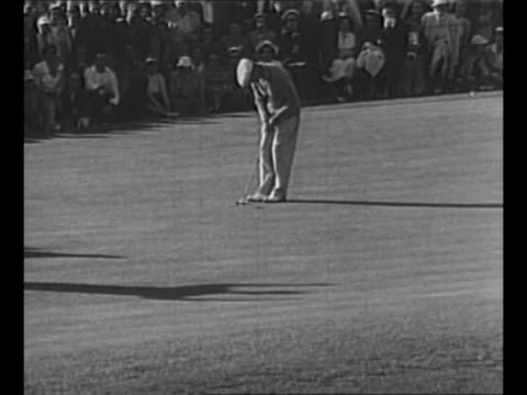 cu golfer ben hogan smiles and winks as he stands on golf course at the 1948 us open / hogan putts / pan gallery watching on side of hill / hogan... - ゴルフのティー点の映像素材/bロール