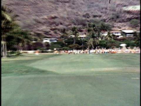 vídeos y material grabado en eventos de stock de golfer, bill kratzert, playing a shot for an eagle to tie for the lead at the hawaiian open golf tournament/ honolulu, oahu, hawaii islands, usa/... - 1978