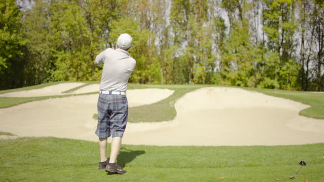 golfer chipping onto the green of a golf course - golf shoe stock videos & royalty-free footage