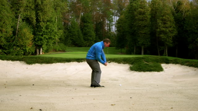 golfer chips ball from sand trap - golf swing stock videos & royalty-free footage