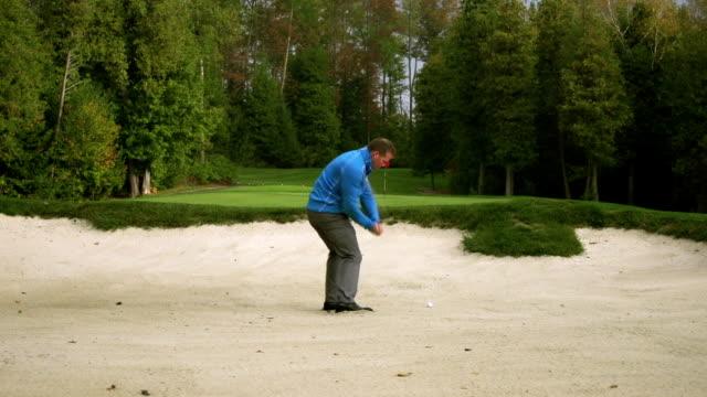vídeos y material grabado en eventos de stock de golfista chips de bola de búnker - swing de golf