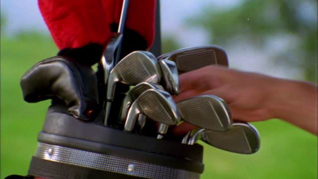 a golfer chooses a club from his bag. - ゴルフクラブ点の映像素材/bロール