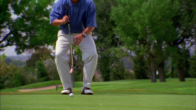 vídeos y material grabado en eventos de stock de a golfer crouches behind his golf ball, then prepares to putt. - putt