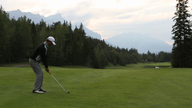 Golfer drives ball down fairway at mountain course
