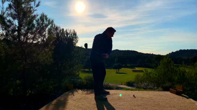 golfer exercising golf swing against sun - golf swing silhouette stock videos & royalty-free footage