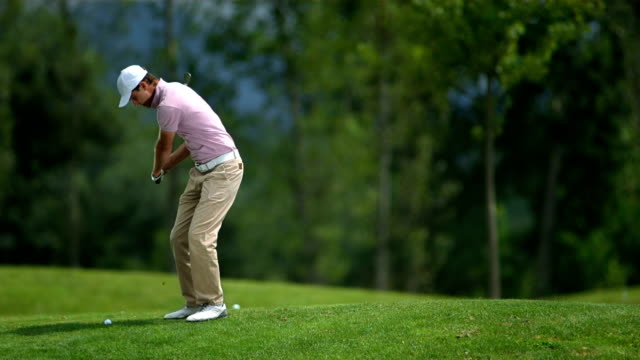 hd slow motion: golfer hits ball - golf swing stock videos & royalty-free footage