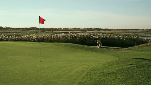 golfer hitting approach shots into green - ショットを決める点の映像素材/bロール