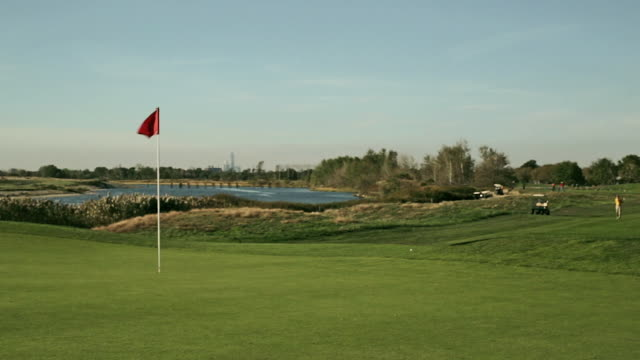 golfer hitting approach shots into green - golfplatz green stock-videos und b-roll-filmmaterial