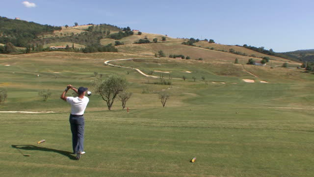 ws golfer hitting ball from tee / saturnia, tuscany, italy - golf shot stock videos & royalty-free footage