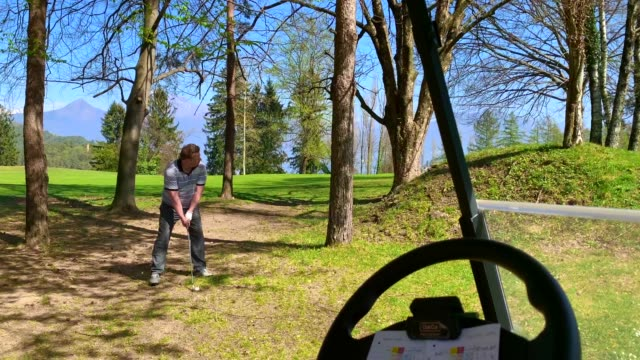 golfer hitting golf ball in the trees - golf shot stock videos & royalty-free footage