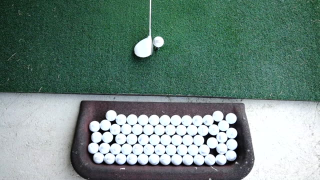 golfer hitting the golf ball on the exercise mat on driving range in switzerland - driving range stock videos & royalty-free footage
