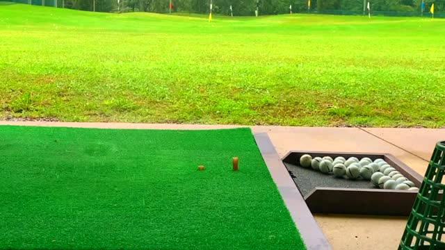 vídeos de stock e filmes b-roll de golfer hitting the golf ball with iron golf club in slow motion on a wet mat in driving range in a rainy day - golf