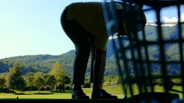 golfer hitting the golf ball with iron on driving range - driving range stock videos & royalty-free footage